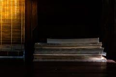 Baixa imagem chave da pilha de livros que ajustam-se na tabela de madeira com luz solar através da cortina no fundo imagem de stock royalty free