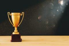 baixa imagem chave do troféu do ouro sobre a tabela de madeira e o fundo escuro, com luzes abstratas do brilho imagens de stock royalty free
