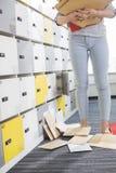 Baixa seção da mulher de negócios que está por originais caídos no vestuário no escritório criativo Imagem de Stock Royalty Free