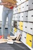 Baixa seção da mulher de negócios que está por originais caídos no vestuário no escritório criativo Foto de Stock Royalty Free