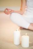 Baixa seção da mulher na pose da ioga com velas iluminadas Foto de Stock Royalty Free