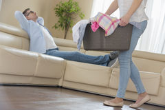 Baixa seção da mulher que anda com cesta de lavanderia quando homem que relaxa no sofá no fundo Fotos de Stock Royalty Free