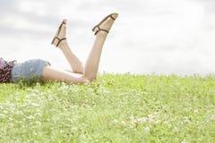 Baixa seção da mulher que encontra-se na grama contra o céu foto de stock royalty free