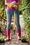 Baixa seção da mulher que está com a forquilha de jardinagem no passeio Fotos de Stock