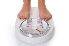 Baixa seção da mulher que está na escala de peso Imagem de Stock Royalty Free