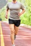 Baixa seção de homem determinado que corre na estrada Fotografia de Stock Royalty Free