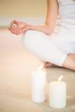 Baixa seção de meditar a mulher com velas iluminadas Fotografia de Stock Royalty Free