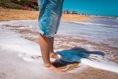 Baixa seção de um homem na praia Foto de Stock