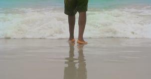 Baixa seção do homem que está na praia 4k filme