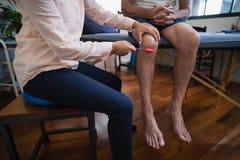 Baixa seção do joelho de exame do terapeuta fêmea com o martelo reflexo no paciente masculino Fotos de Stock