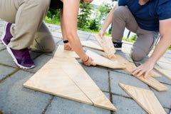 Baixa seção dos amigos que resolvem o enigma de madeira das pranchas no pátio Foto de Stock
