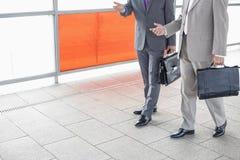 Baixa seção dos homens de negócios que comunicam-se ao andar na estação de estrada de ferro Fotos de Stock Royalty Free