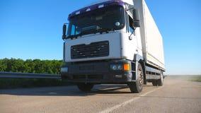 Baixa vista do caminhão com o reboque da carga que conduz na estrada e que transporta bens Equitação do caminhão através do campo filme