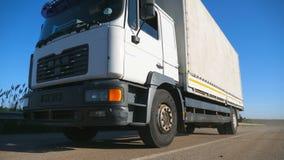 Baixa vista do caminhão com o reboque da carga que conduz na estrada e que transporta bens Equitação do caminhão através do campo video estoque