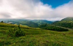 Baixas nuvens acima do campo montanhoso fotografia de stock royalty free
