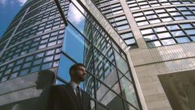 Baixo ângulo do centro de negócios alto com o homem de negócios que está próximo video estoque