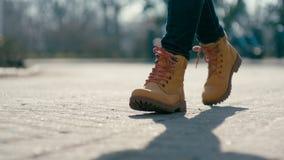 Baixo-ângulo do close-up que segue o tiro da mulher irreconhecível nas botas que anda adiante video estoque
