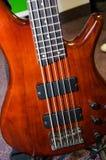 Baixo bonito da guitarra, sob a cor vermelha brilhante imagem de stock