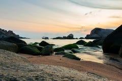 Baixo ponto de vista do molde nas rochas na praia durante o nascer do sol Fotos de Stock