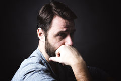 Baixo retrato chave do homem que senta-se na obscuridade e Fotografia de Stock