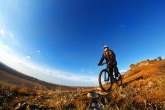 Baixo, retrato largo do ângulo contra o céu azul do motociclista da montanha que vai para baixo Ciclista no equipamento e no capa Foto de Stock Royalty Free