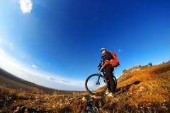 Baixo, retrato largo do ângulo contra o céu azul do motociclista da montanha que vai para baixo Ciclista no equipamento e no capa Fotos de Stock