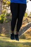 Baixo-seção da corda de salto da mulher no parque foto de stock