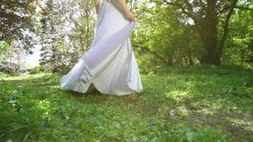 Baixo tiro da mulher no vestido longo que gerencie ao redor no jardim verde no movimento lento filme