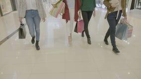 Baixo tiro do grupo de pés fêmeas que anda na entrada da alameda quando sacos de compras levando em suas mãos - filme