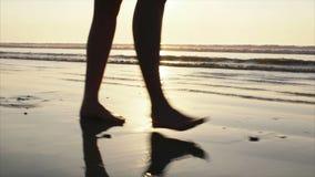 Baixo vídeo da seção da mulher descalça que anda na areia molhada durante o por do sol video estoque