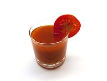 Baixo vidro do suco de tomate com um segmento do tomate Fotografia de Stock Royalty Free