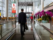 BAIYUN, CANTON, CINA - 10 MARZO 2019 – punto di vista posteriore di un viaggiatore in vestito che cammina verso il suo portone di fotografia stock
