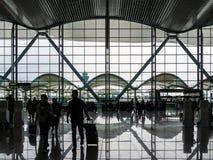 BAIYUN, GUANGZHOU, CHINA - 10 BRENG 2019 in de war – silhouetteert mening van reizigers die de Internationale vertrekzaal van Bai royalty-vrije stock foto