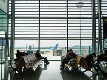 BAIYUN, GUANGZHOU, CHINA - 10 DE MARZO DE 2019 - pasajeros sentarse y esperar en una puerta de embarque dentro del aeropuerto int fotografía de archivo