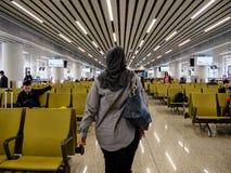BAIYUN, GUANGZHOU, CHINA - 10 DE MARZO DE 2019 - una mujer musulmán en hijab/pañuelo camina a su puerta de embarque en Baiyun int fotos de archivo libres de regalías