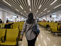 BAIYUN, GUANGZHOU, CHINA - 10 MAR 2019 - A Muslim woman in hijab / headscarf walks to her boarding gate at Baiyun International royalty free stock photos