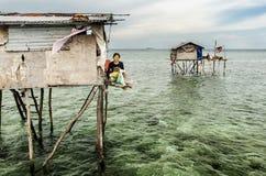 Bajau坐她的沙巴的Semporna,马来西亚的部落母亲木房子 免版税库存图片
