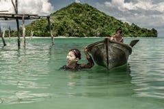Bajau拉扯有她的兄弟的部落女孩小船坐里面对她的房子在Semporna海村庄,沙巴Semporna,马来西亚 库存图片