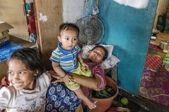 Bajau睡觉她的有她的女儿和儿子的,沙巴Semporna,马来西亚房子外的部落母亲 库存图片