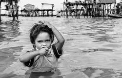 Bajau站在迷路到他的房子海,沙巴Semporna,马来西亚的中部的部落男孩画象  库存照片
