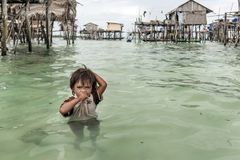 Bajau站在迷路到他的房子海,沙巴Semporna,马来西亚的中部的部落男孩画象  库存图片