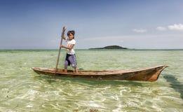 Bajau部落孩子获得乐趣通过荡桨小船在他们的村庄房子附近在海,沙巴Semporna,马来西亚 免版税库存图片