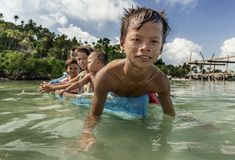 Bajau部落孩子获得乐趣通过荡桨小船在他们的村庄房子附近在海,沙巴Semporna,马来西亚 免版税库存照片