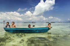 Bajau部落孩子获得乐趣通过荡桨小船在他们的村庄房子附近在海,沙巴Semporna,马来西亚 库存照片