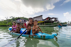 Bajau children relax on a dug out boat near shoreline in Sabah, Malaysia. Stock Photo