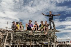 Bajau kids still on a wooden plank and showing hand gestures to tourist, Sabah Semporna, Malaysia. Semporna, Malaysia June 2015: The Bajau Laut people, or `sea stock images