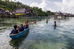 Bajau-Kinder entspannen sich auf einem gegrabenen heraus Boot nahe Küstenlinie in Sabah, Malaysia Stockfotografie