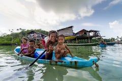 Bajau-Kinder entspannen sich auf einem gegrabenen heraus Boot nahe Küstenlinie in Sabah, Malaysia Stockfoto