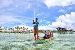 Bajau Laut在一条小船哄骗在马伊加海岛  图库摄影