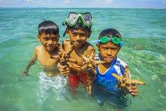 Bajau não identificado Laut caçoa em um barco na ilha de Maiga Foto de Stock Royalty Free